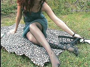 A sexy amateur redhead shows off her feet while reading outside